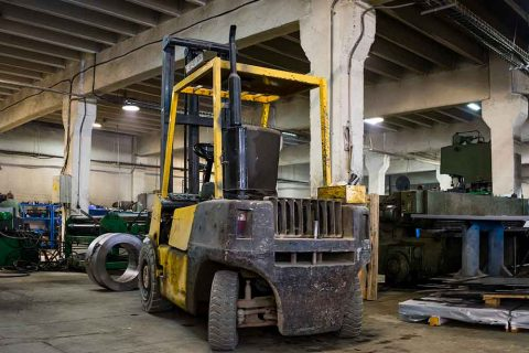 forklift-parked-inside-an-industrial-hall-PYQLENB